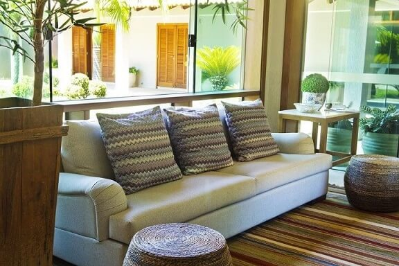 Sala de estar com puff redondo de vime Projeto de Joel Caetano Paes