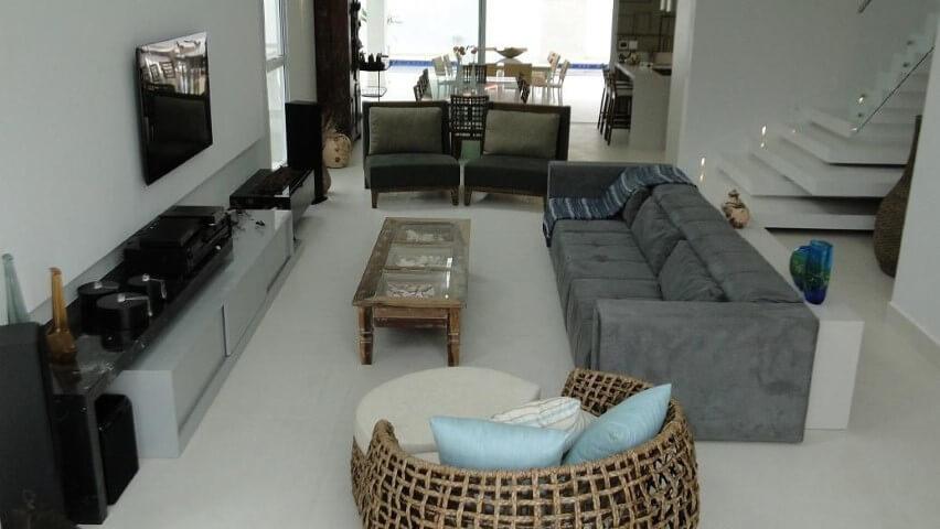 Sala de estar com puff redondo de vime Projeto de Natalia Pini