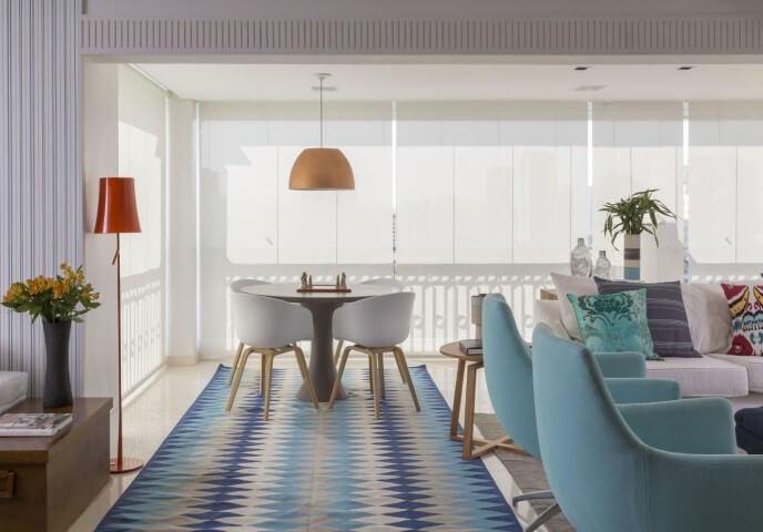 Sala integrada com tapete e cadeiras em tons de azul Projeto de Ih Designers