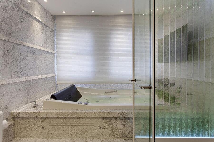 banheiro com banheira de hidro com revestimento de mármore carrara