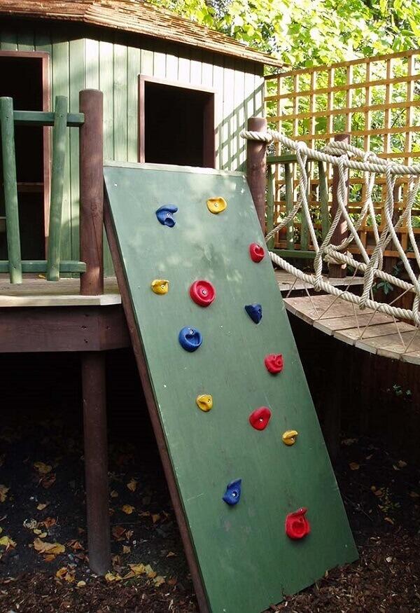 Paredão de escalada colorido dá acesso a entrada para a casa na árvore