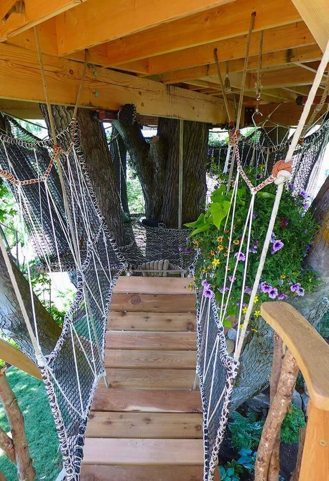 Aproveite o espaço embaixo da casa na árvore para incluir uma ponte de madeira