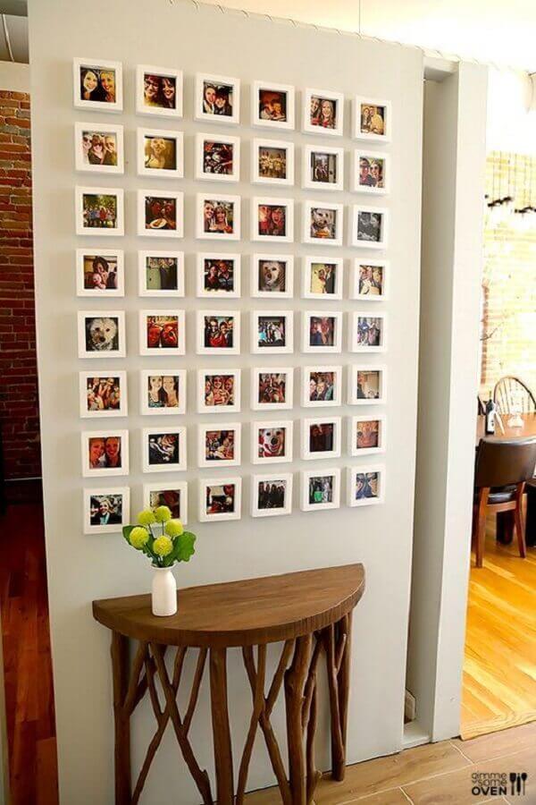 decoração com mural de fotos na parede com molduras brancas