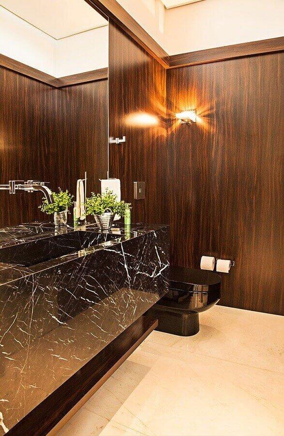 decoração lavabo com parede revestida de madeira e cuba esculpida em mármore preto