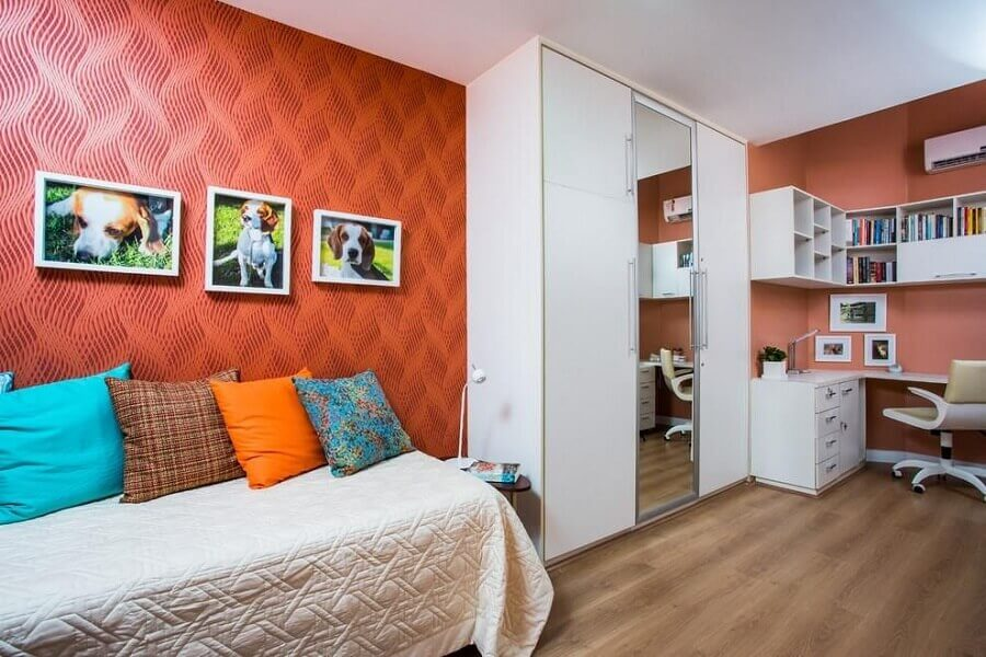 quarto de solteiro com parede vermelha e guarda roupa solteiro branco com portas de correr