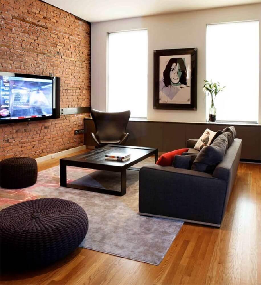 decoração sala de TV com parede de tijolinho e piso de madeira