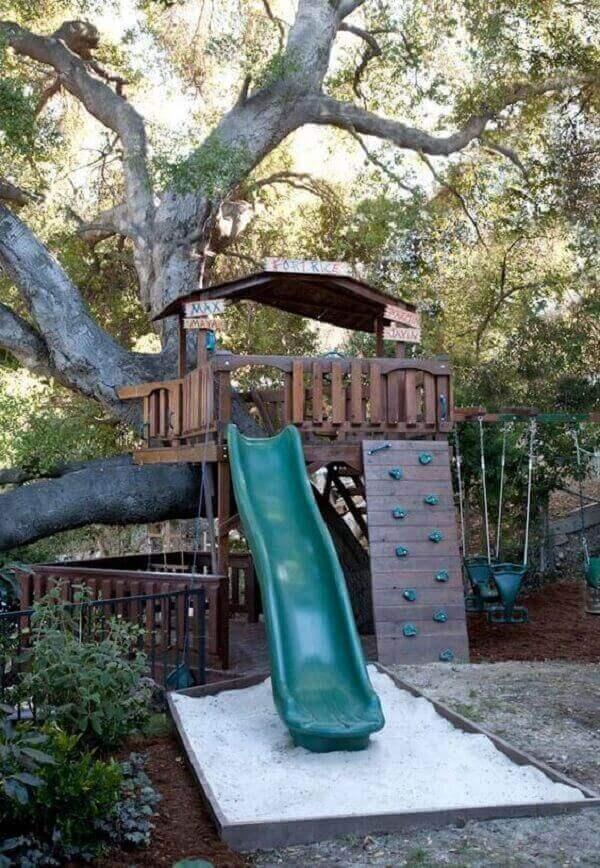Aproveite a área de lazer pequena para construir uma linda casa na árvore com paredão de escalada, escorregador e balanços