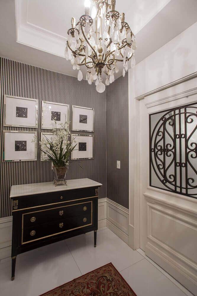 hall de entrada decorado com papel de parede e lustre