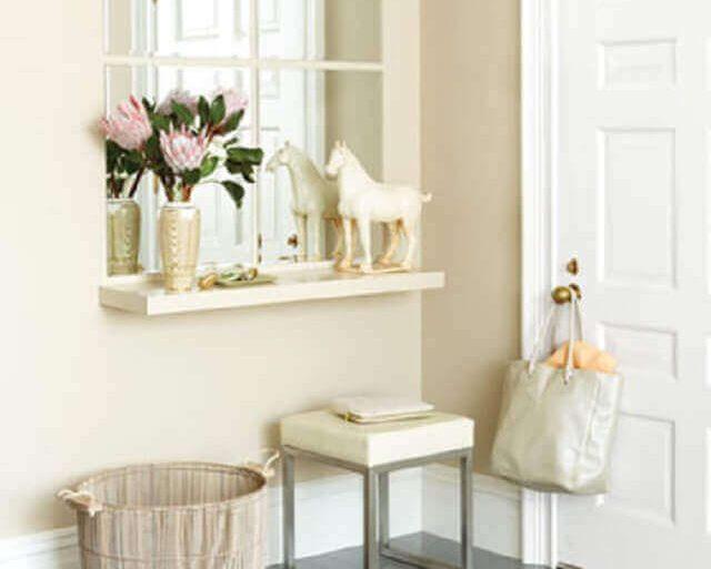 hall de entrada pequeno decorado com tons neutros aparador e espelho