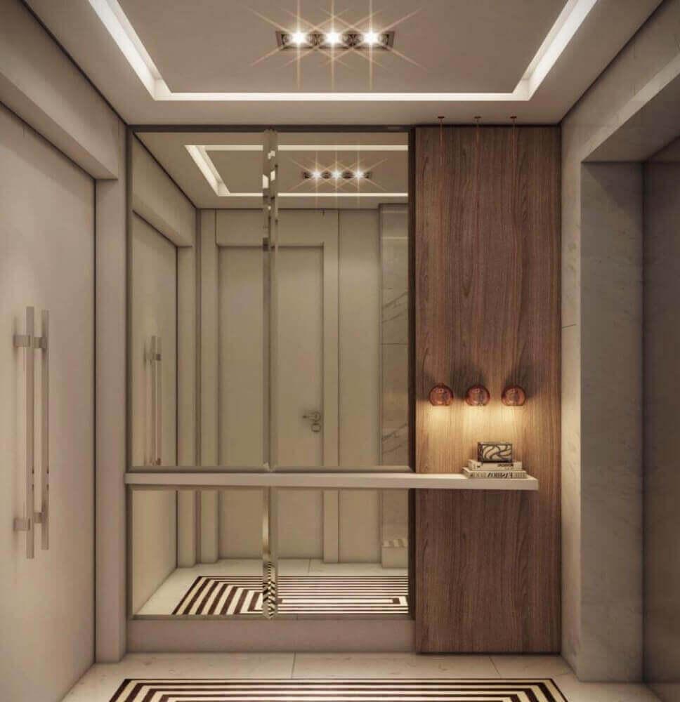 hall de entrada residencial com parede espelhada e bancada branca