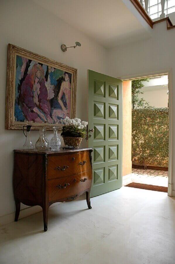 hall de entrada residencial decorado com quadro e aparador antigo