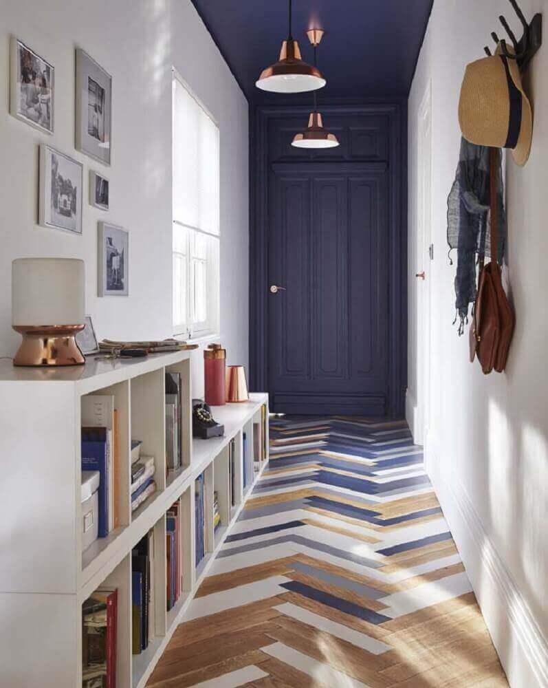 hall de entrada residencial tipo corredor com nichos para livros e cabideiro de parede