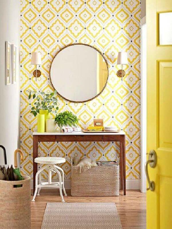 hall decorado com papel de parede amarelo e espelho redondo