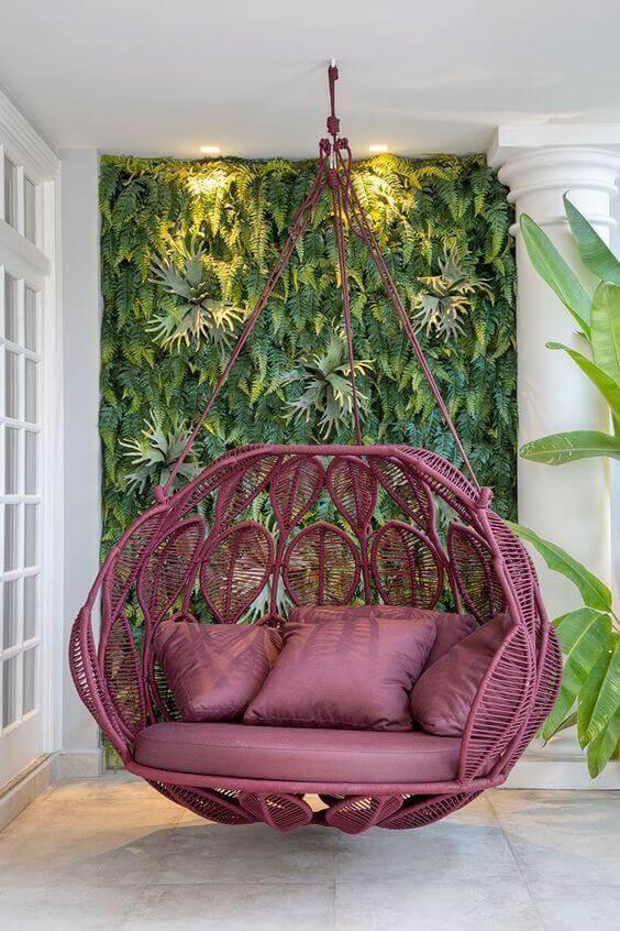 Paredes decoradas com jardim vertical com cadeira giratória fixa no teto