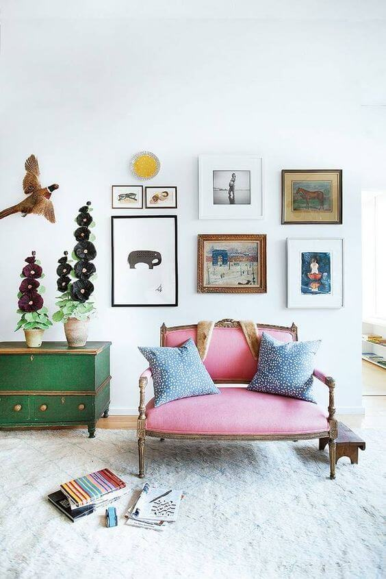 Paredes decoradas com quadros e sofá rosa