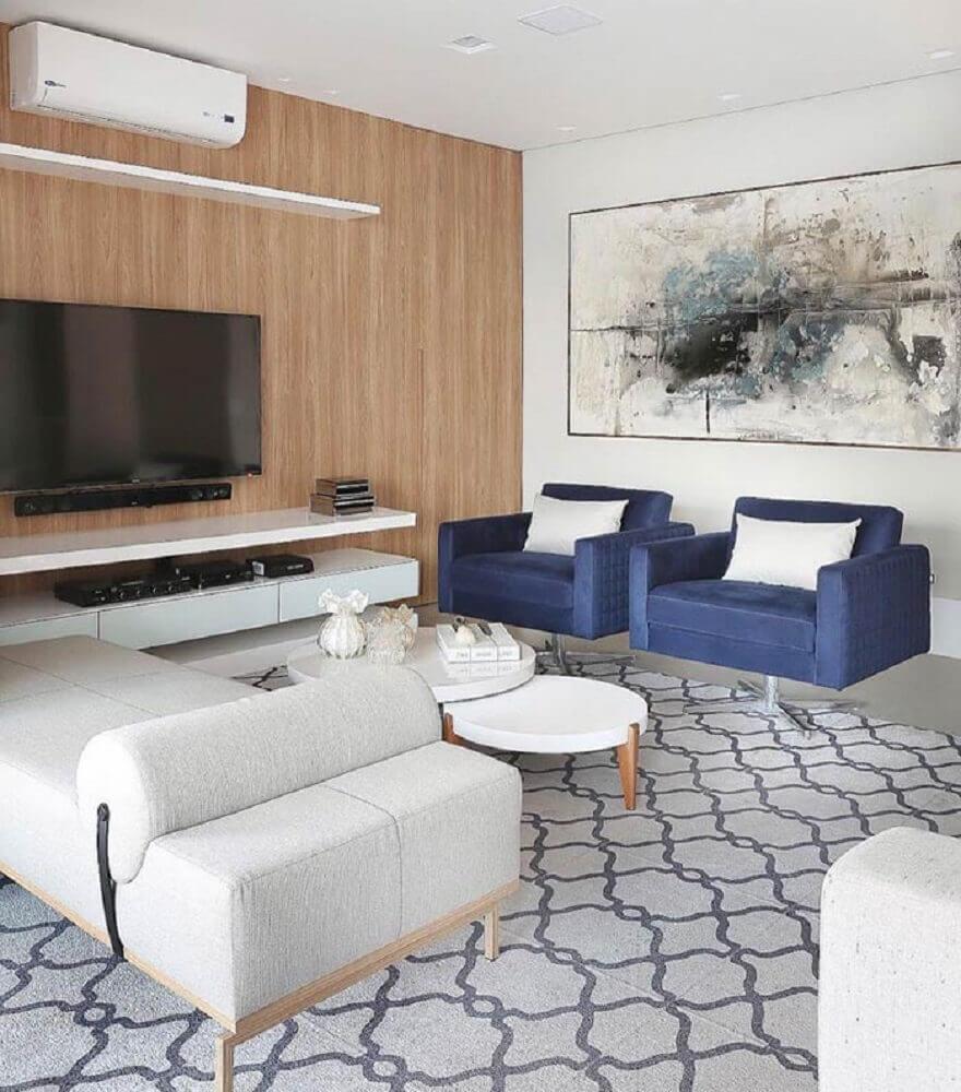 Quadros grandes para sala de estar com poltrona azul e parede revestida de madeira