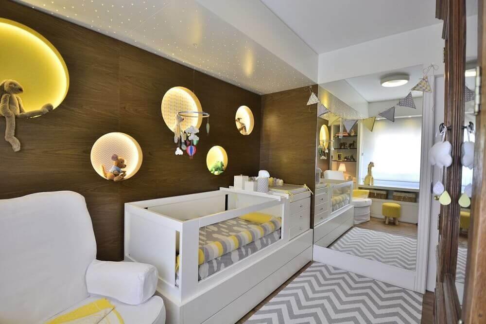 quarto de bebê pequeno planejado com painel de madeira e nichos com iluminação embutida