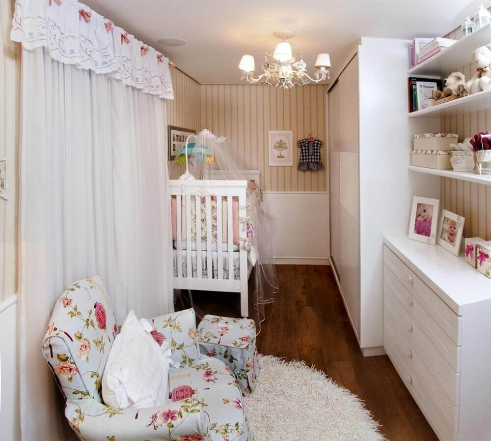 quarto de bebê pequeno planejado com papel de parede listrado e poltrona de amamentação com estampa floral