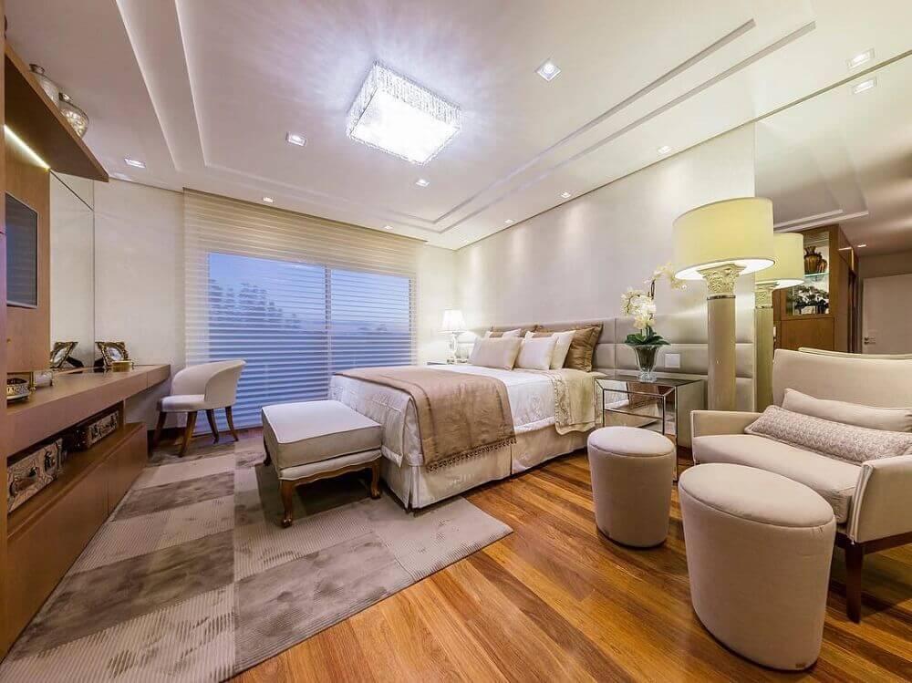 quarto decorado com paleta de cores bege e piso de madeira
