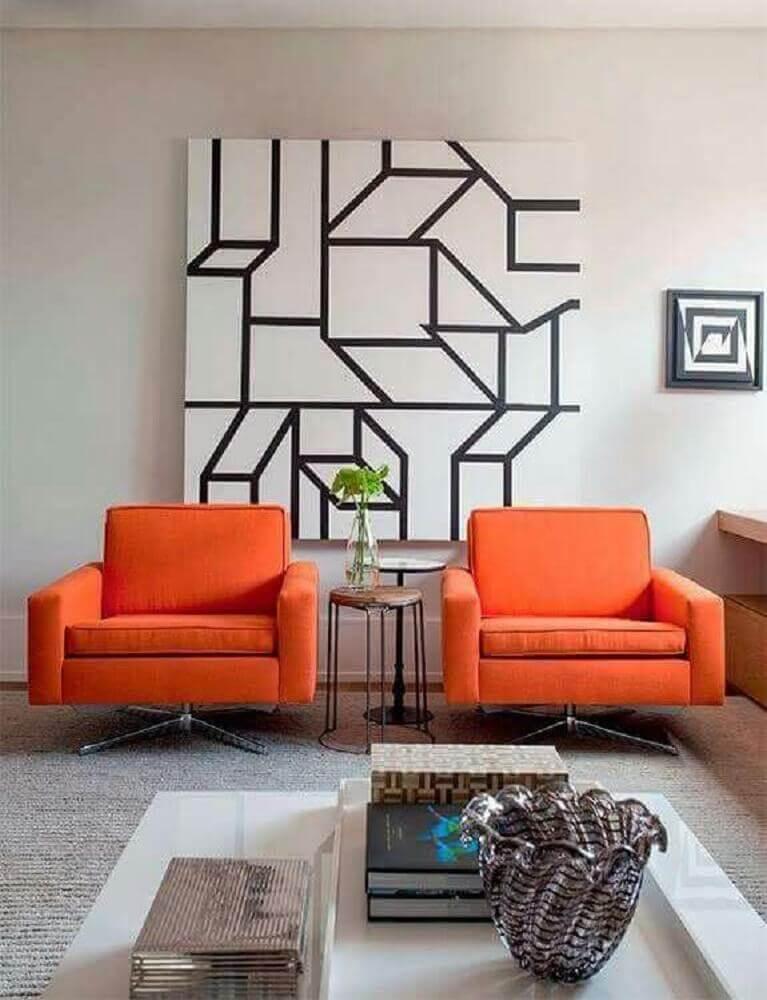 sala de estar decorada com poltronas laranjas e quadros decorativos grandes