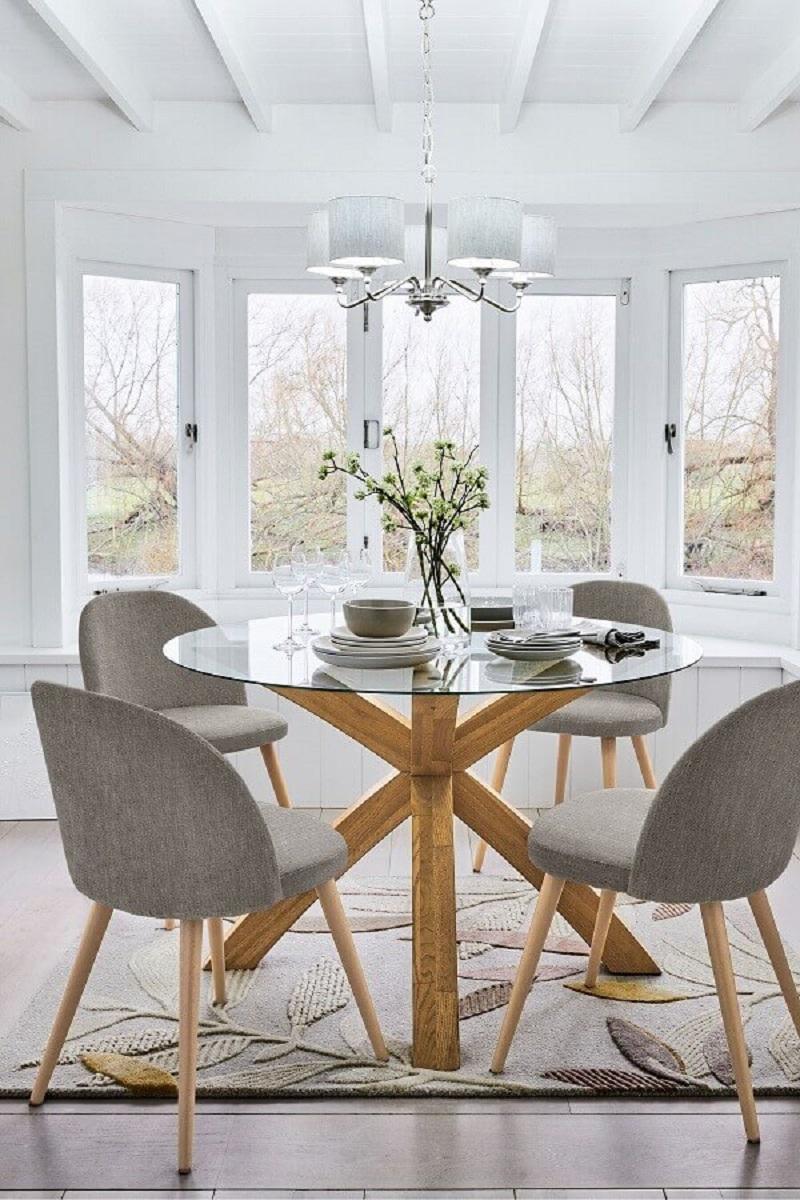 sala de jantar branca decorada com mesa de vidro redonda com base de madeira e cadeiras cinza estofadas Foto Pinterest
