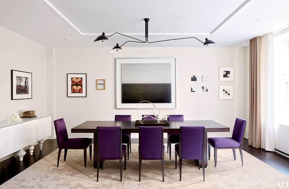 sala de jantar com cadeiras roxas e quadro grande