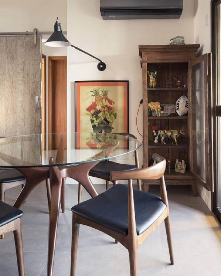 sala de jantar decorada com mesa de vidro redonda com base moderna de madeira  Foto Histórias de Casa