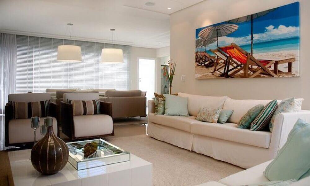 sala toda decorada em tons claros com quadro decorativo grande e colorido