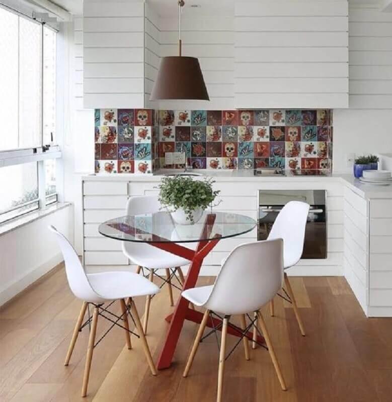 varanda gourmet decorada com mesa redonda de vidro com base vermelha moderna  Foto Planète Déco