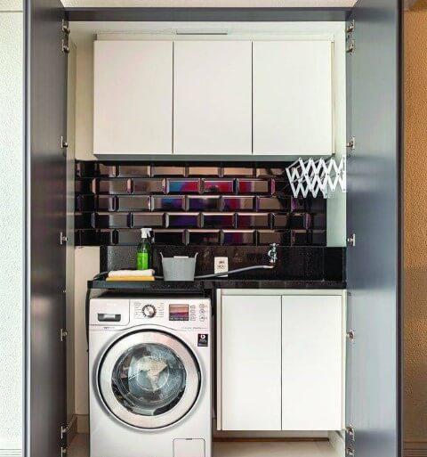 Área de serviço pequena com armários brancos e revestimento preto Foto de Mauricio Gebara Arquitetura