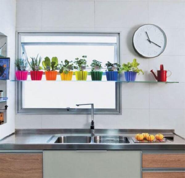 A prateleira de vidro acima da pia serve de apoio para a horta da cozinha