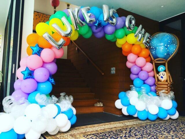 Arco de bexiga colorido com base parecendo nuvens Foto de That Balloons
