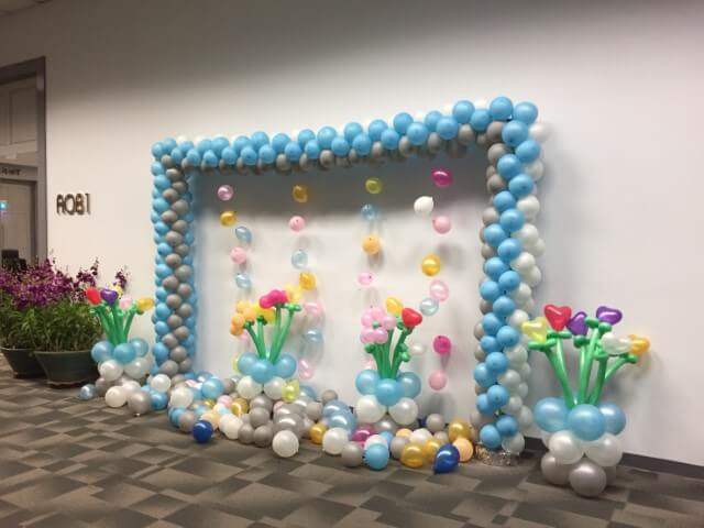 Arco de bexiga na parede formando moldura com flores Foto de Miracle Balloon