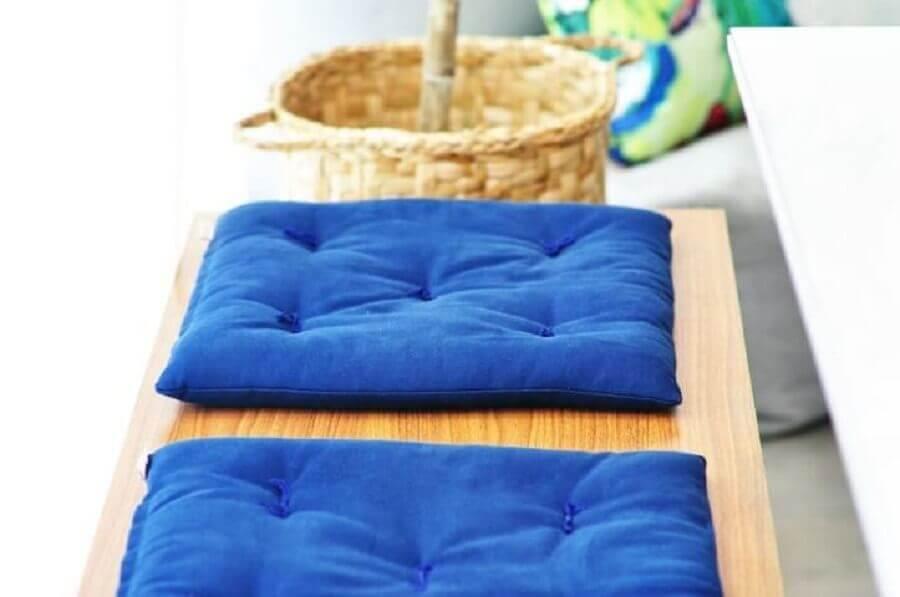 Banco de madeira com almofadas em azul royal Foto Condecorar