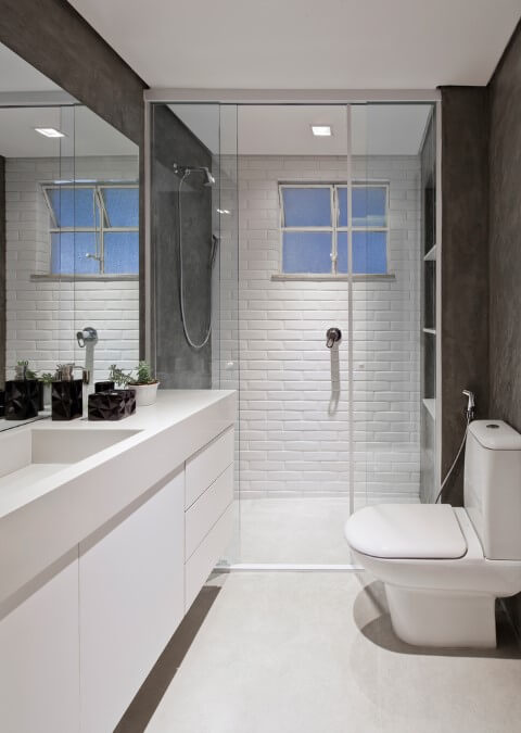 Banheiro moderno com paredes de cimento queimado e parede de subway tiles Foto de ArchDaily