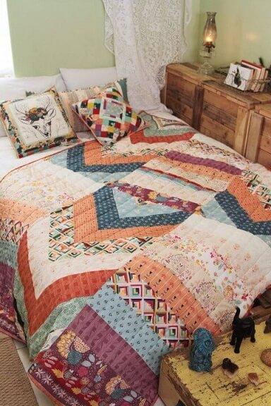 Colcha e almofadas de patchwork sobre a cama