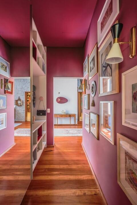 Corredor com parede em tons de rosa com quadros Projeto de AMC Arquitetura