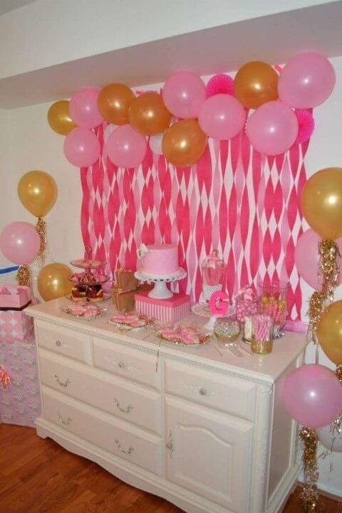 Decoração com papel crepom rosa atrás da mesa do bolo Foto de Pinterest