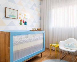 Decoração de quarto de bebê com papel de parede e berço que mistura madeira e azul- Foto Studio Novak