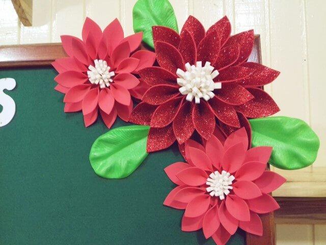 Flores de EVA vermelhas em quadro verde