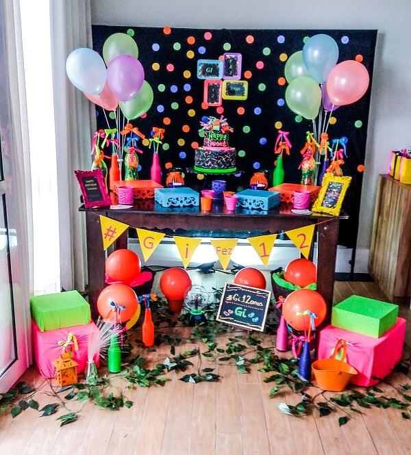 O móvel de madeira trouxe neutralidade para a decoração da festa neon