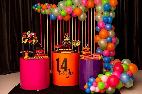 A mesa do bolo pode receber uma decoração especial com balões