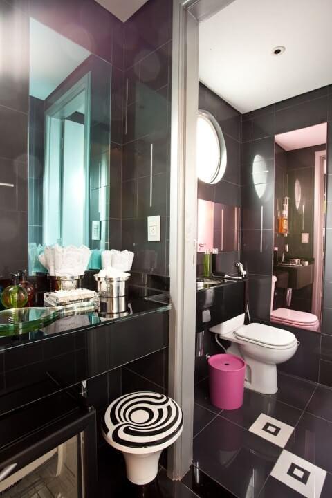 Lavabo preto e branco com espelho e lixeira em tons de rosa Projeto de Brunete Fraccaroli