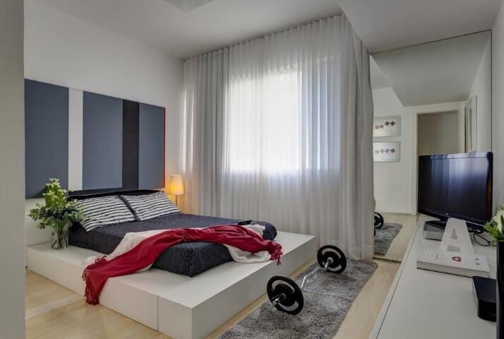 Loft com quarto de casal com espelho na parede Projeto de Denise Macedo