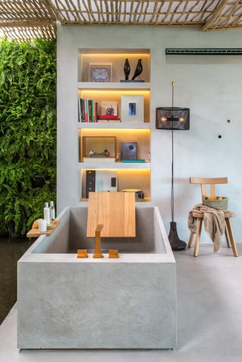 Loft com sala de banho aberta com banheira de concreto Projeto de Gisele Taranto