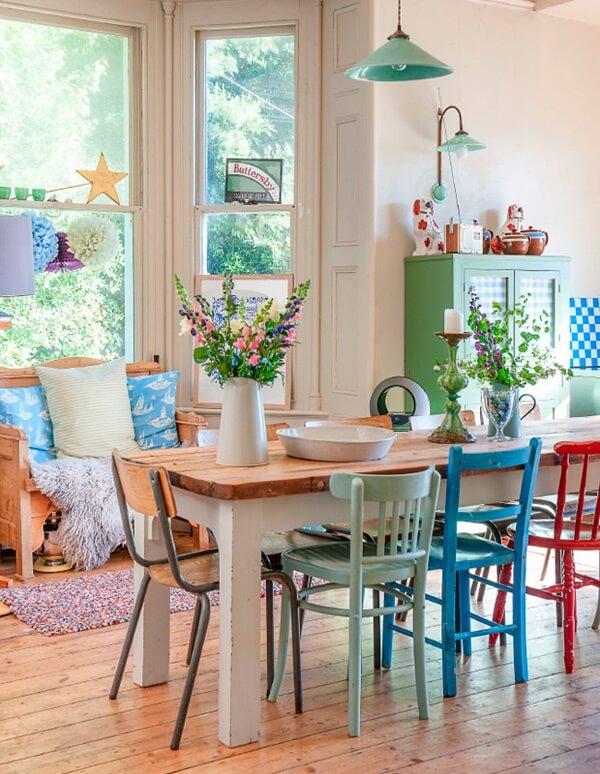 Mesa para sala de jantar com tampo de madeira e cadeiras coloridas