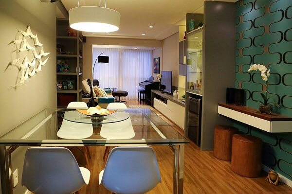 Mesa para sala de jantar feita em vidro posicionada próxima a parede