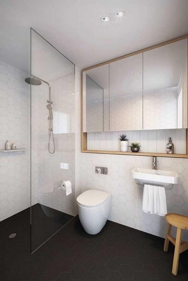 Nesse projeto, a moldura de madeira do espelho acomoda um nicho para banheiro discreto na parte inferior
