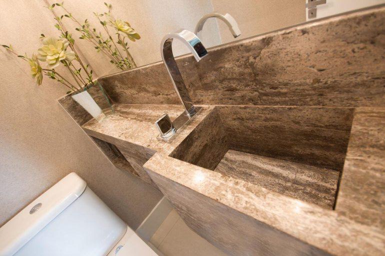 Os banheiros decorados com pia esculpida na pedra ganham um toque de elegância