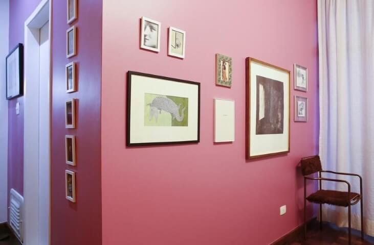 Parede em tons de rosa com quadros decorativos Projeto de Buji